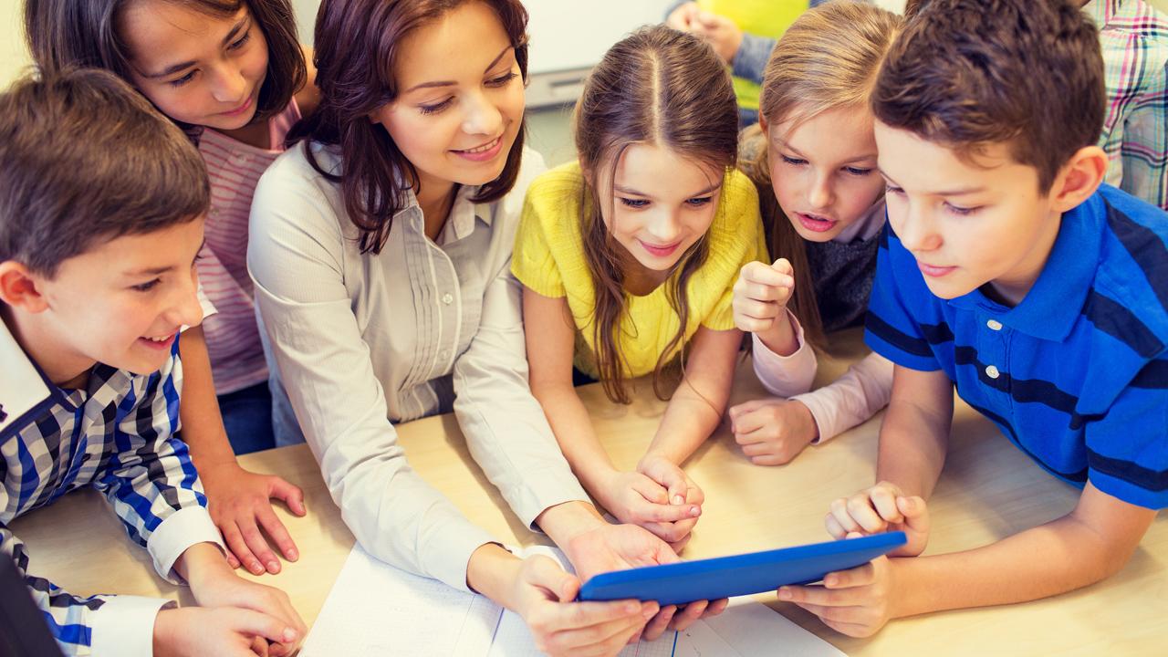 Zdjęcie nauczycielki z uczniami patrzącymi w ekran tabletu