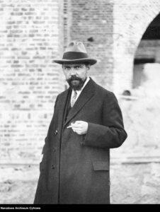 Kazimierz Ulatowski, inżynier architekt. Fotografia sytuacyjna w kapeluszu, płaszczu i papierosem w ręku