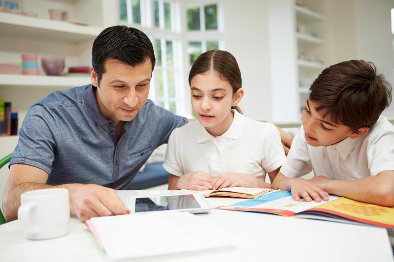 Ojciec pomaga dzieciom w lekcjach