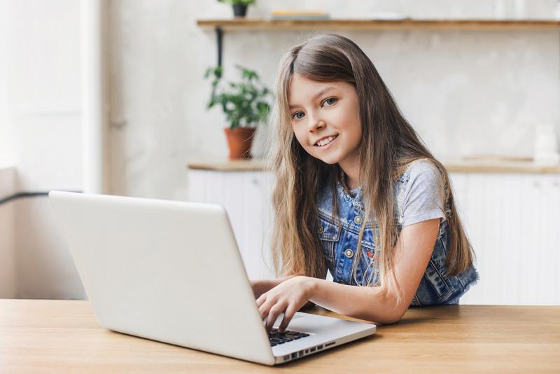 Uczennica korzysta z komputera w domu