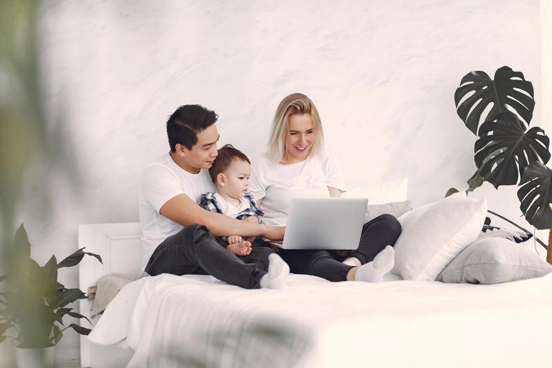 Rodzice z małym dzieckiem przy laptopie, Canva