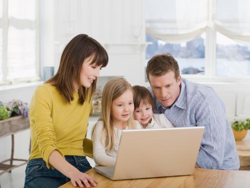 Rodzice z dziećmi przy laptopie, Canva