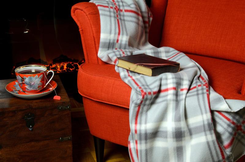 Fotel, na oparciu przewieszony koc. Obok kubek herbaty