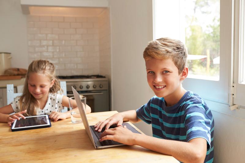 Dziewczynka i chłopiec siedzą przy stole. Dziewczynka używa tabletu, a laptopa
