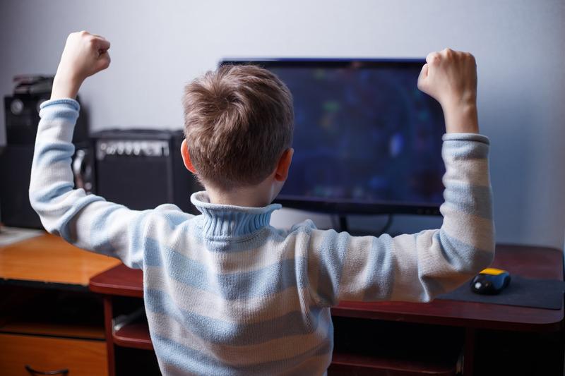 Chłopiec cieszy się ze zwycięstwa w grze internetowej