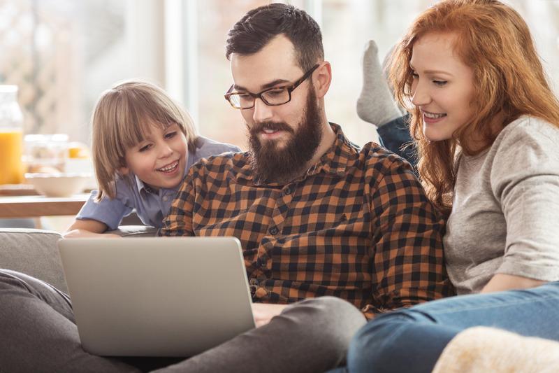 Rodzice i syn oglądaą film na laptopie