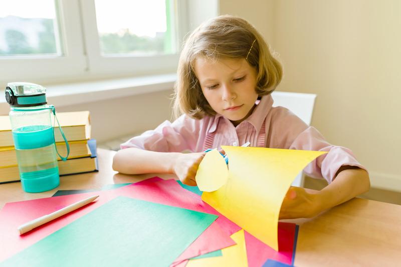 Dziewczynka wycina coś z kolorowego papieru