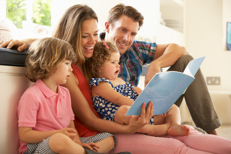 Rodzice siedzą na kanapie z dziećmi i czytają im książkę