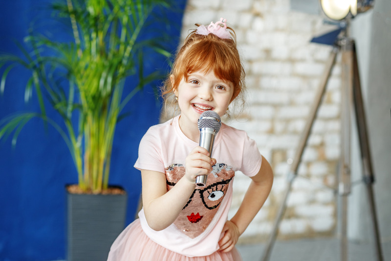 Uśmiechnięta dziewczynka śpiewa piosenkę