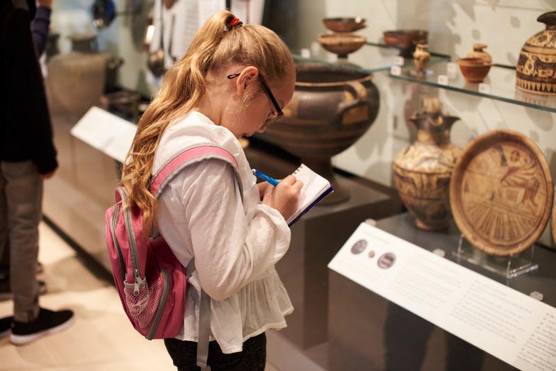 Dziewczynka w muzeum przygląda się eksponatom i robi notatki