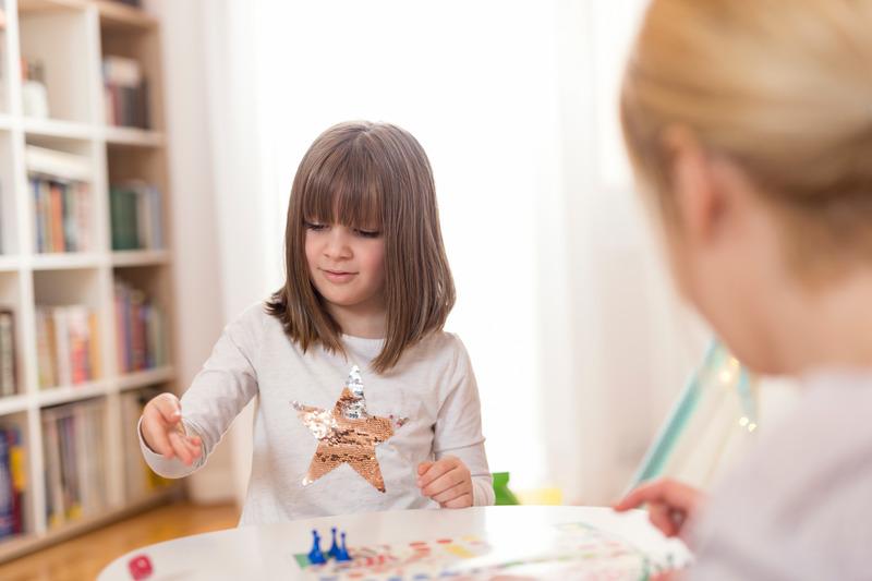 Matka i córka grają w grę planszową. Córka rzuca kostką do gry