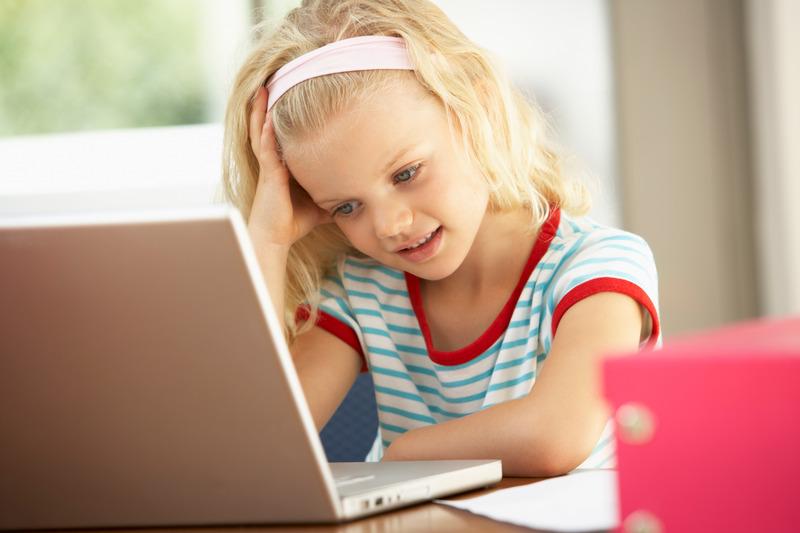 Dziewczynka uczy się w domu, korzystając z laptopa