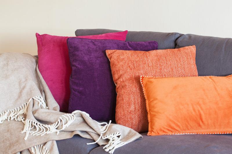 Kolorowe poduszki i koc na kanapie