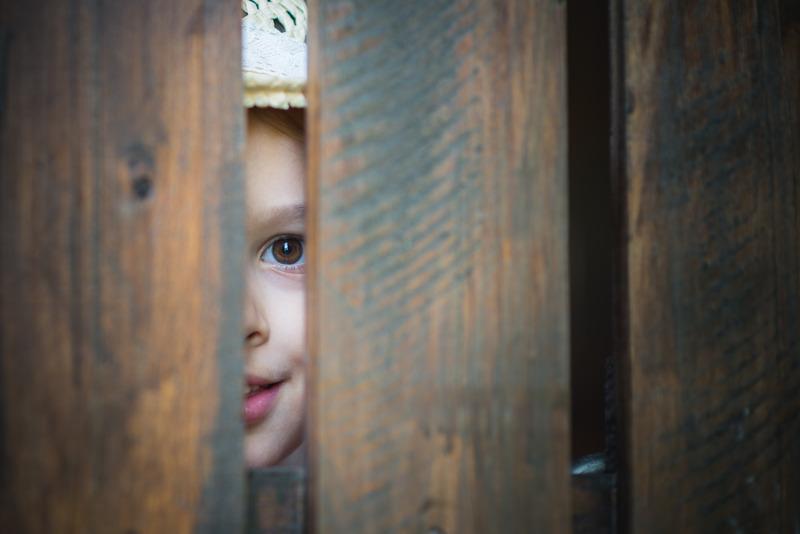 Ciekawska dziewczynka zagląda przez szparę w drewnianym płocie