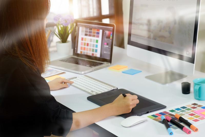 Projektant grafiki komputerowej wykonuje projekt za pomocą tabletu graficznego