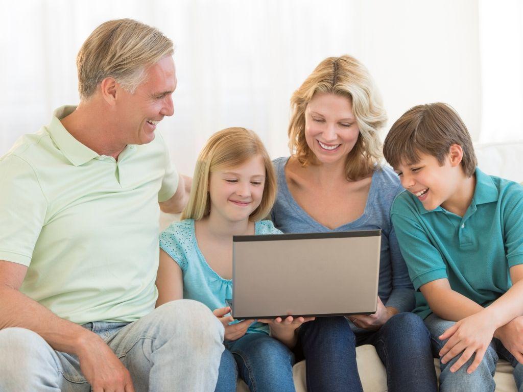 Rodzice i dzieci korzystają z laptopa