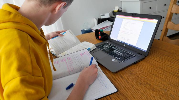 Uczeń pracuje przy laptopie
