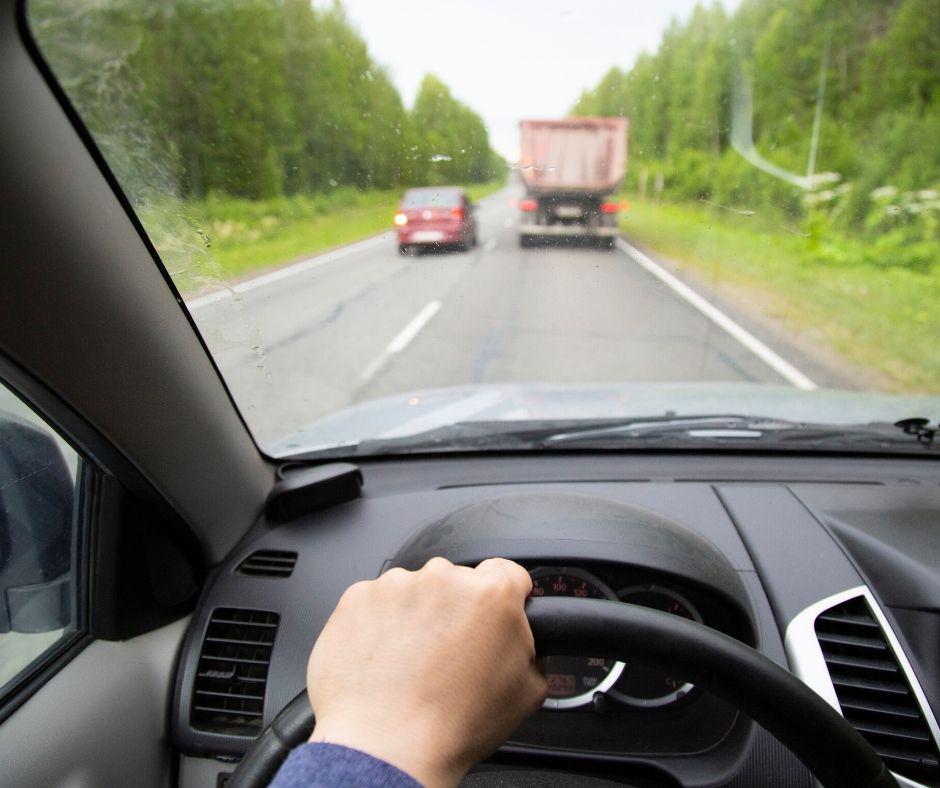 Kierowca obserwuje samochód osobowy wyprzedzający ciężarówkę
