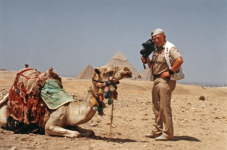 Na zdjęciu Tony Halik z kamerą obok wielbłąda na tle piramidy