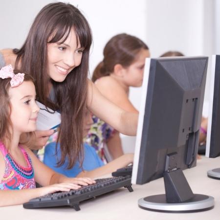 Nauczyciel z dziećmi przy komputerze