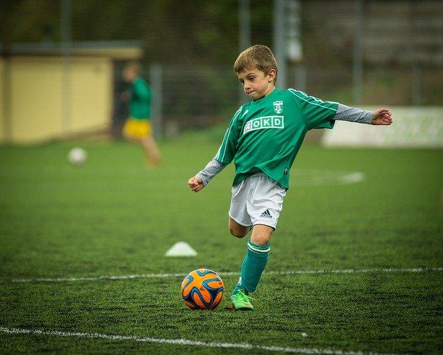 chłopiec gra w piłkę nożną