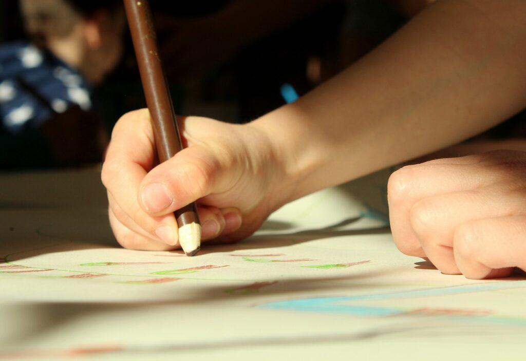 ręce dziecka rysującego kredką