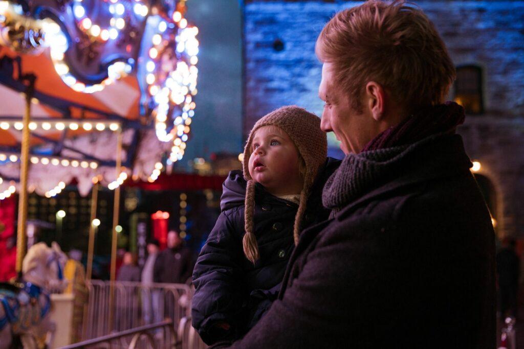 mężczyzna z dzieckiem na ręku; oboje patrzą na karuzelę